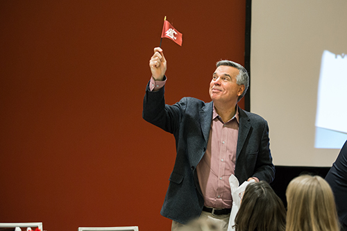 man waves a small WSU flag at the SPA annual meeting