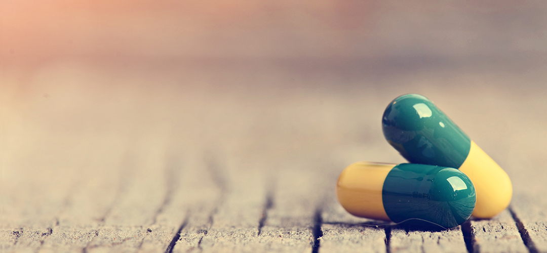 detail image of two pill capsules displayed on wood background